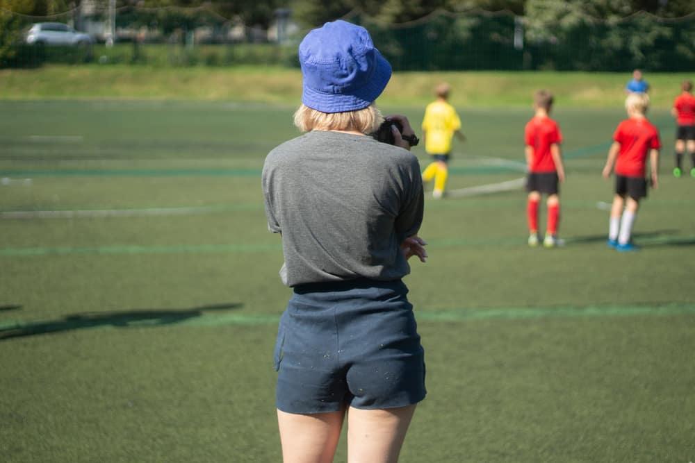 A woman watching a football match wearing soffe shorts.