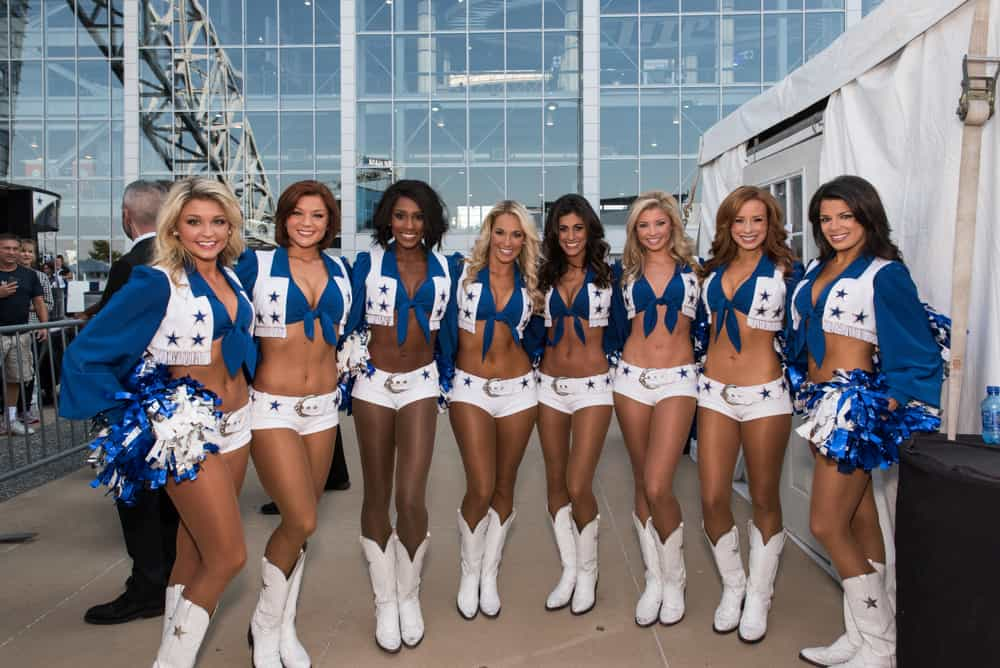 This is a close look at a group of cheerleaders wearing cowboy boots and soffe shorts.