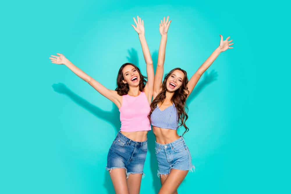 Two women wearing tank tops and denim shorts.
