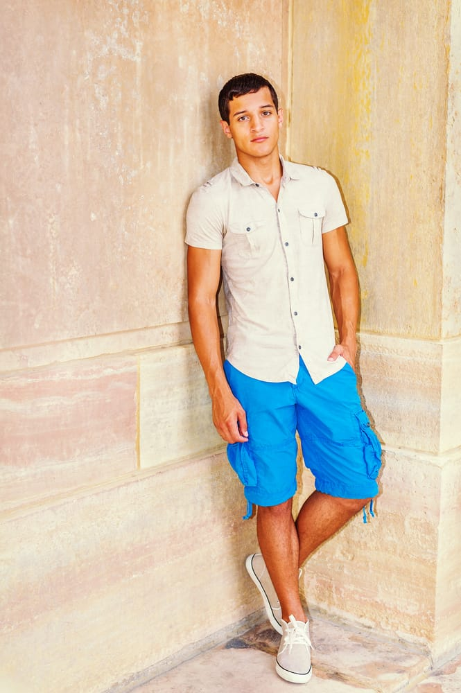 This is a close look at a man wearing a pair of turquoise blue cargo shorts with a button-down shirt.