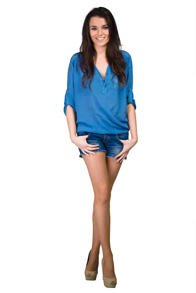 A woman wearing a blue blouse with her blue denim shorts.