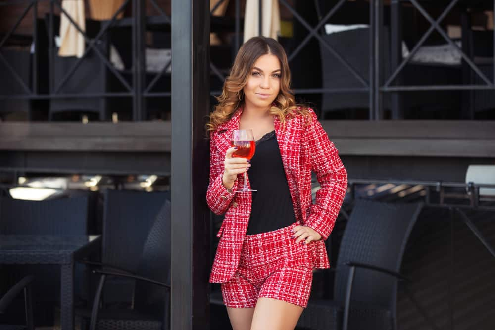 A woman wearing matching red shorts and blazer.