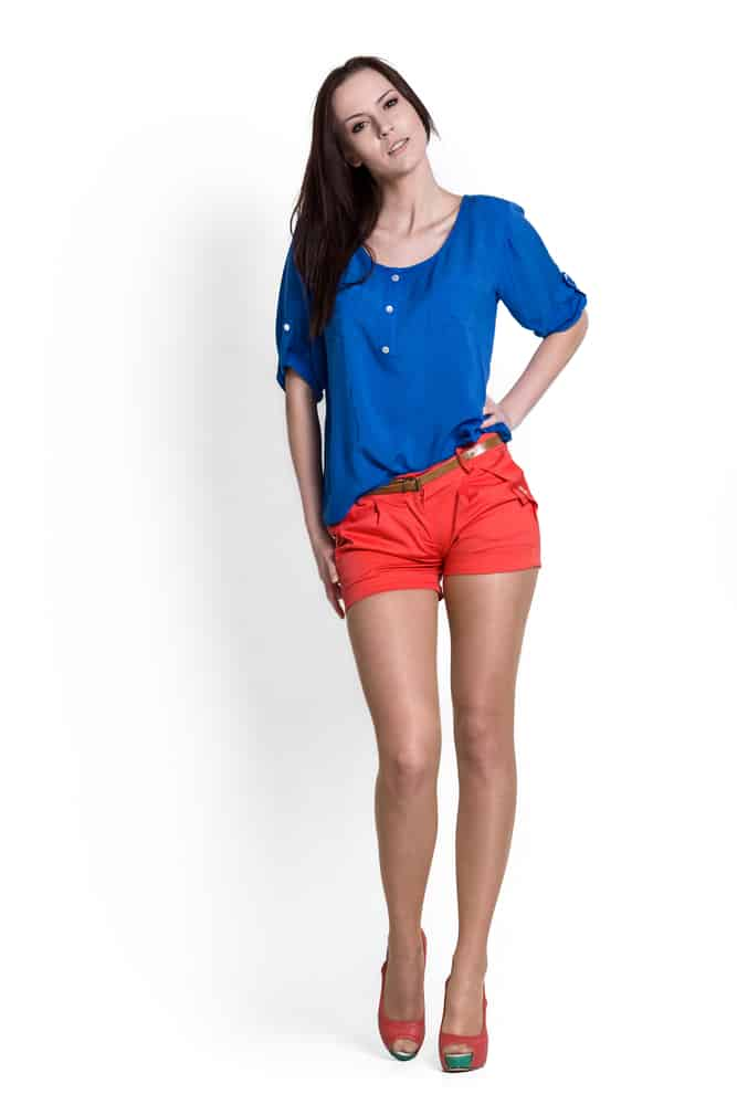A woman wearing a pair of red short shorts and a blue blouse.