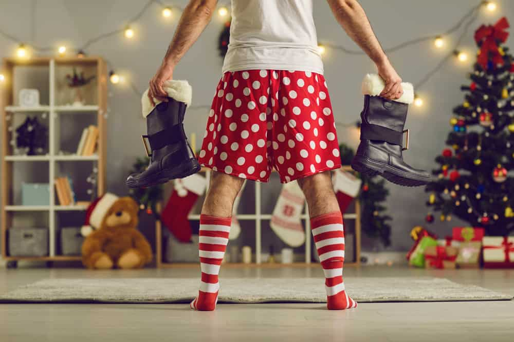 A man wearing a pair of red polka dotted shorts while holding a pair of boots.