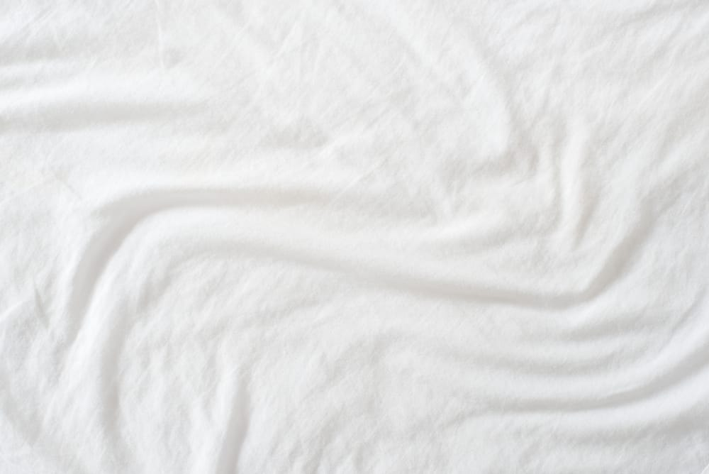 This is a close look at a white crumpled bed sheet.