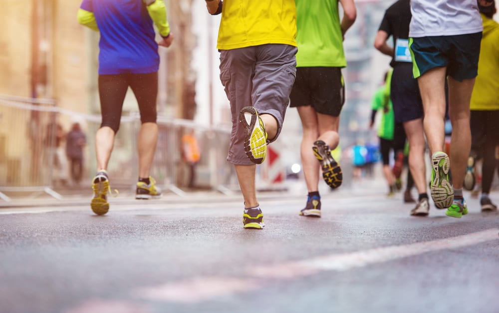 A group of people jogging while wearing various shorts and running shoes.