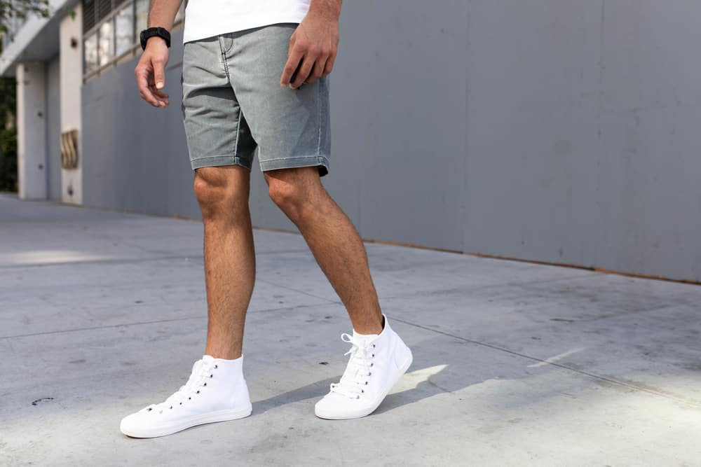 This is a close look at a man wearing ankle-high sneakers with his denim shorts.
