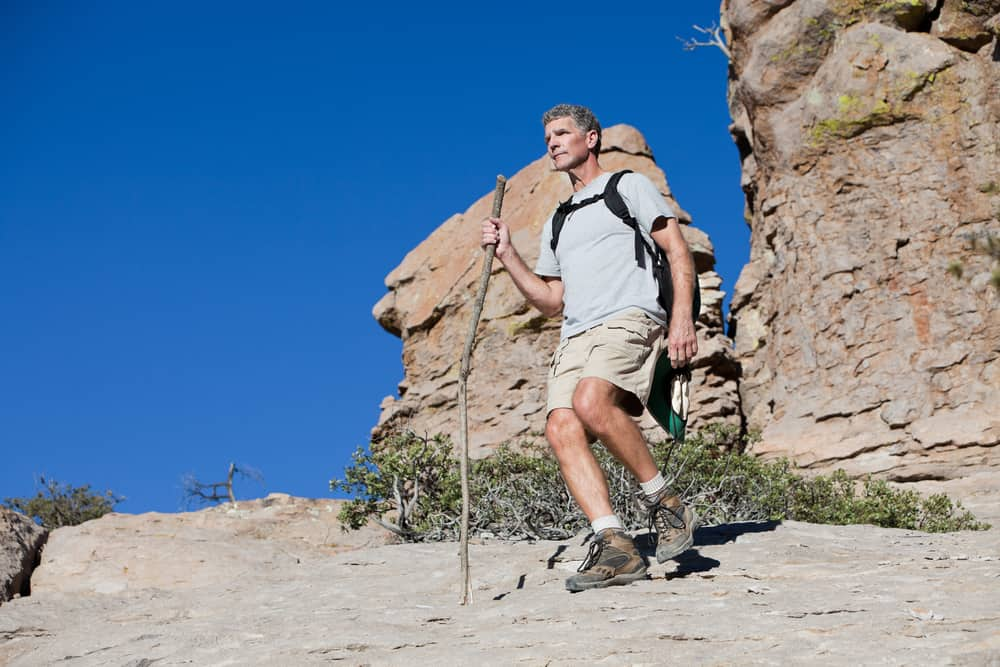 A man hiking on a mountain trail wearing desert boots.