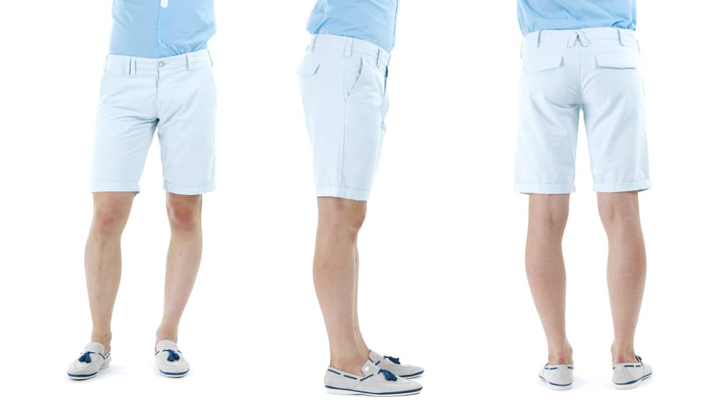 This is a close look at a man wearing a pair of blue tailored shorts and moccasins.