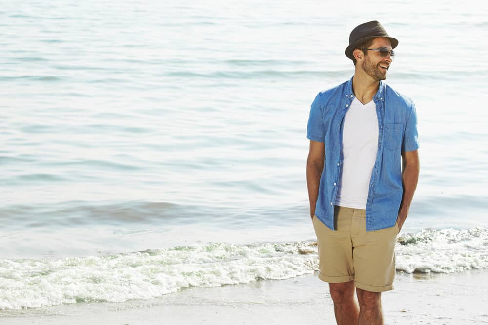 This is a close look at a man wearing a pair of khaki shorts at the beach.