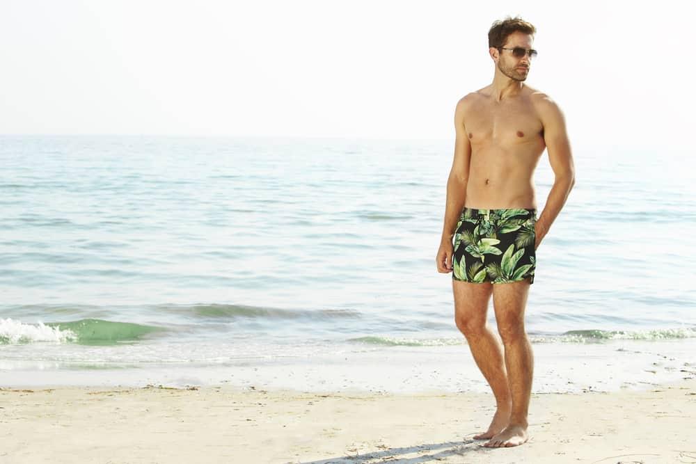 A close look at a man wearing a pair of printed short shorts at the beach.