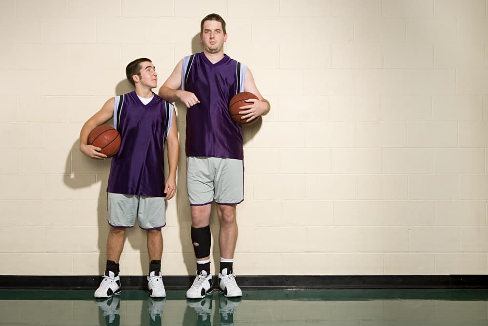 A close look at two men wearing basketball uniforms.