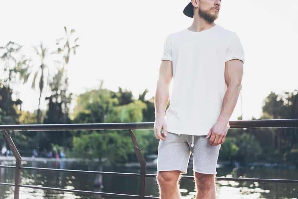 This is a close look at a man wearing a pair of gray drawstring shorts at the park.