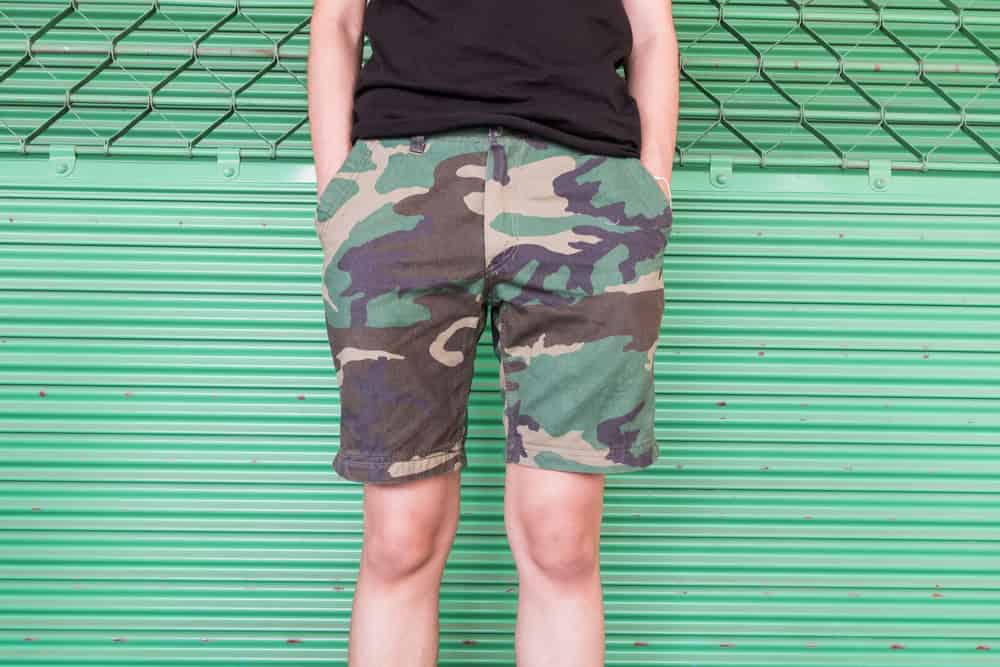 This is a close look at a man wearing a pair of printed camouflage shorts.