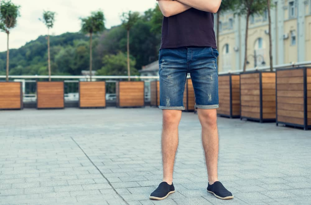 This is a close look at a man wearing a pair of jean shorts.