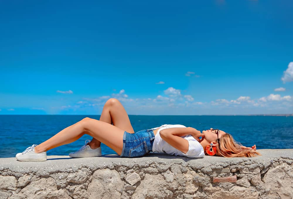 A close look at a stylish woman wearing shorts on the concrete barrier of the sea.