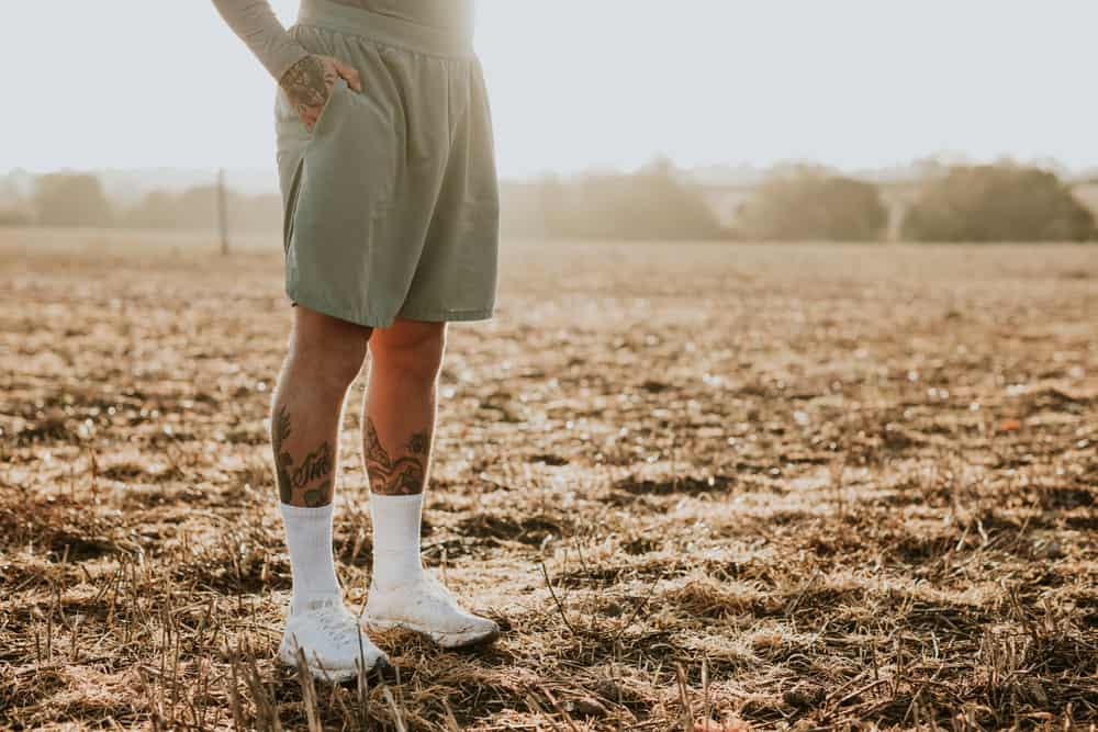 This is a close look at a tattooed man standing on a field wearing running shorts.