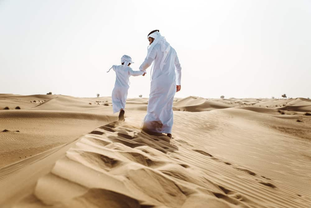 An Arabic man with his son on the desert.