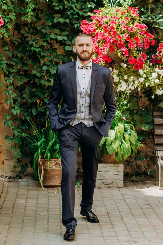 Man in white tie dress standing against the floral backdrop.