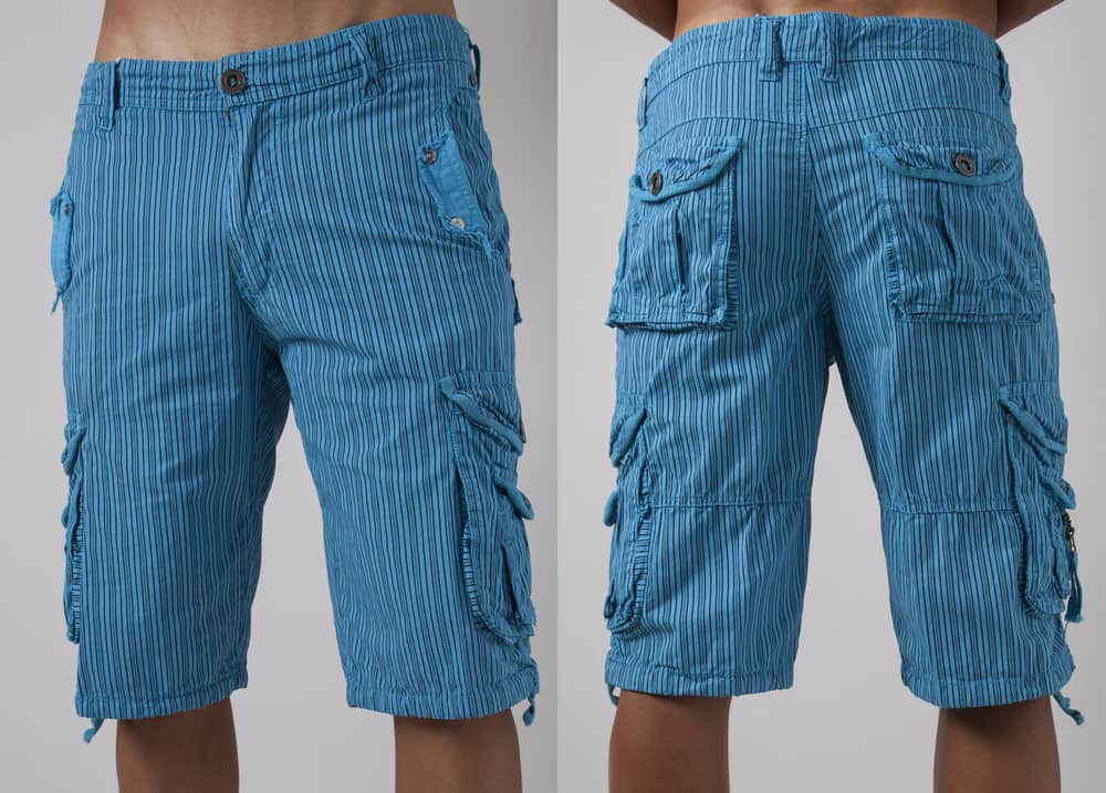 This is a close look at a man wearing a pair of long striped cargo shorts.