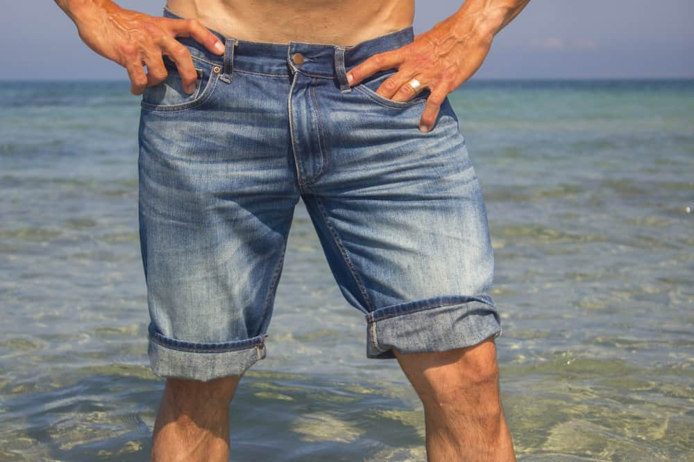 This is a close look at a man wearing a pair of jean shorts at the beach.