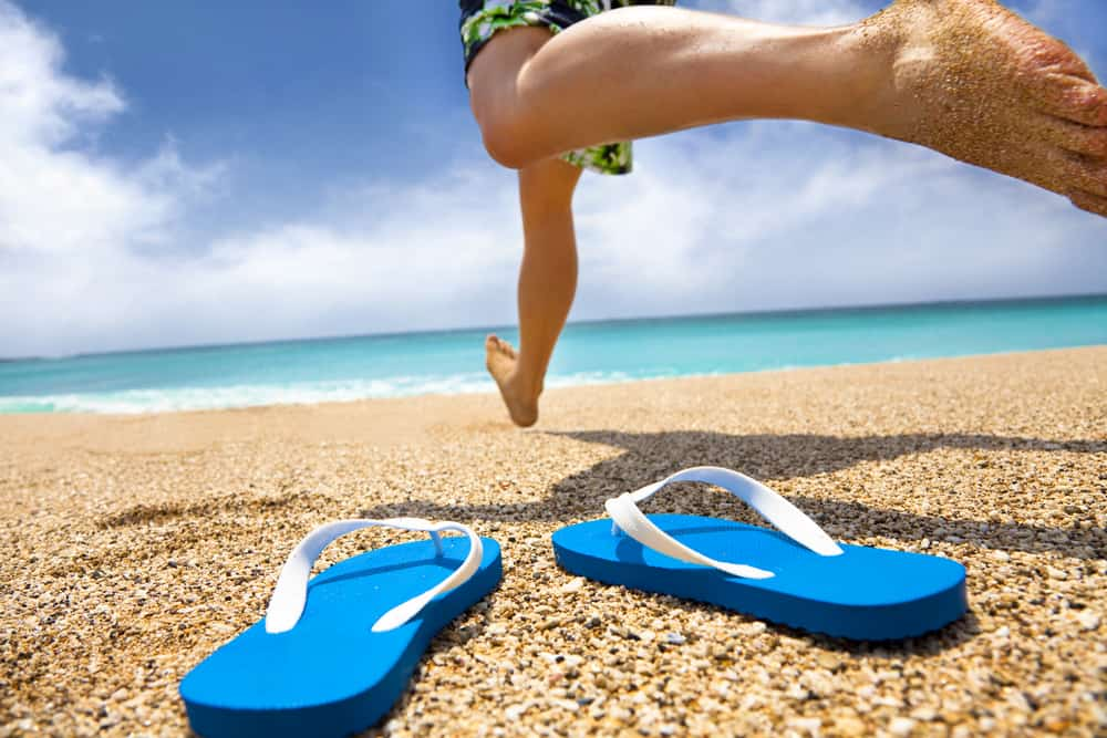 This is a close look at a man leaving his flip-flops by the beach.
