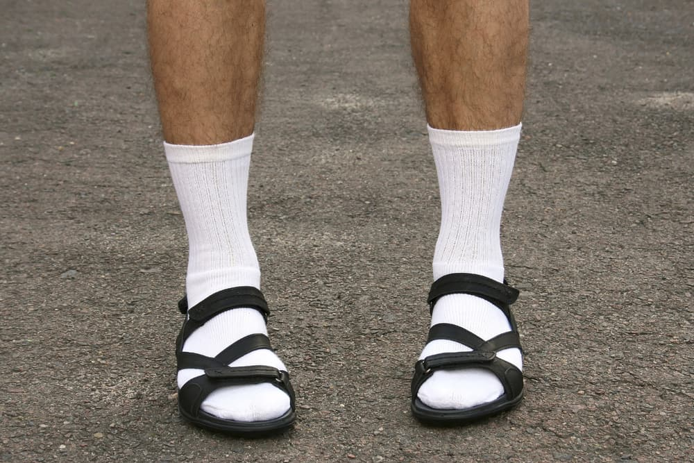 A close look at a man wearing socks and sandals.