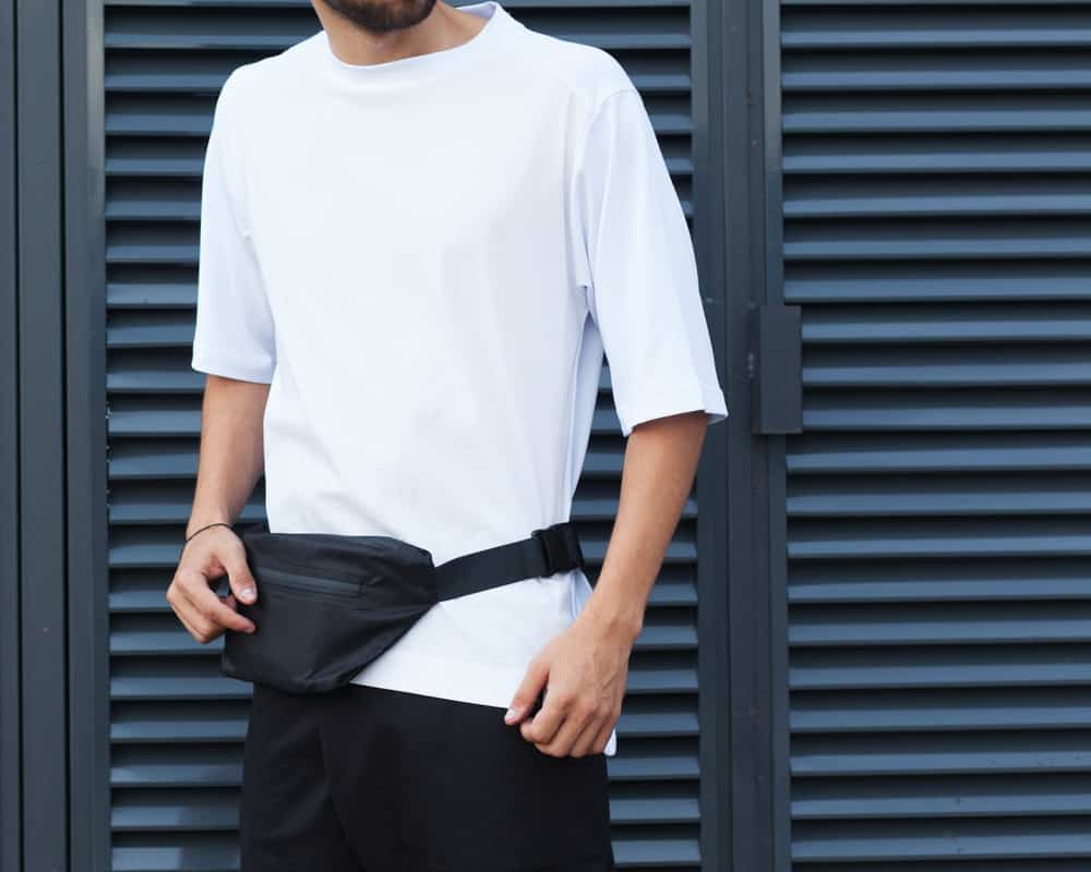 This is a close look at a man wearing a white shirt and a black fanny pack.