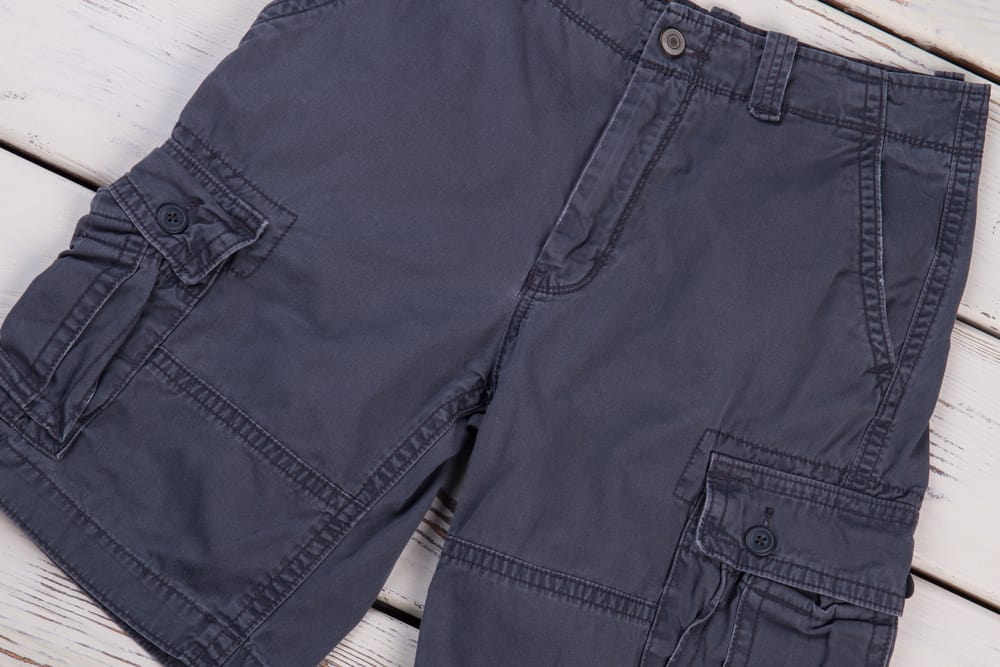 This is a close look at a pair of dark gray men's cargo shorts.