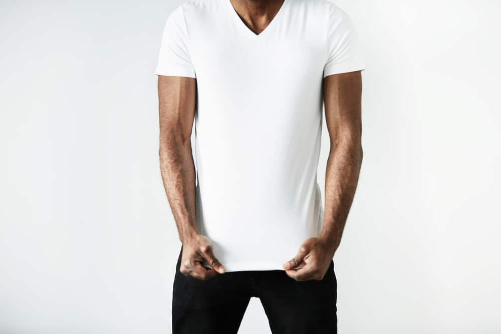 This is a close look at a man wearing a white shirt with his black pants.