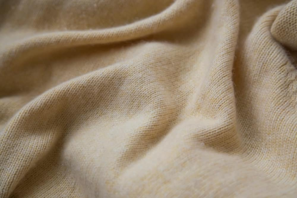 This is a close look at a soft beige cashmere sweater.