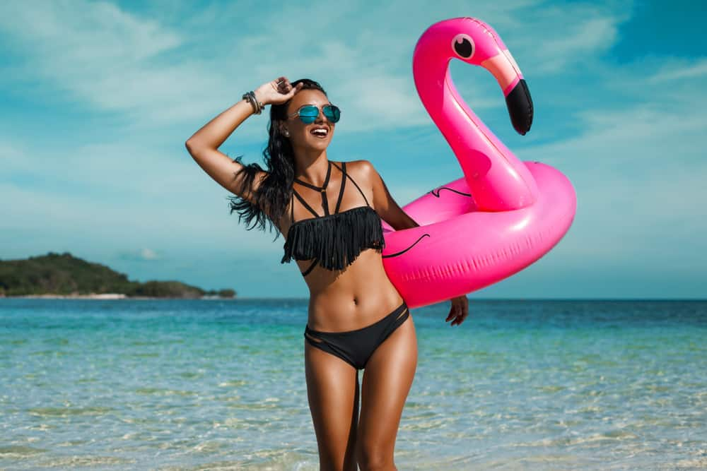 A woman at the beach wearing black bikini.