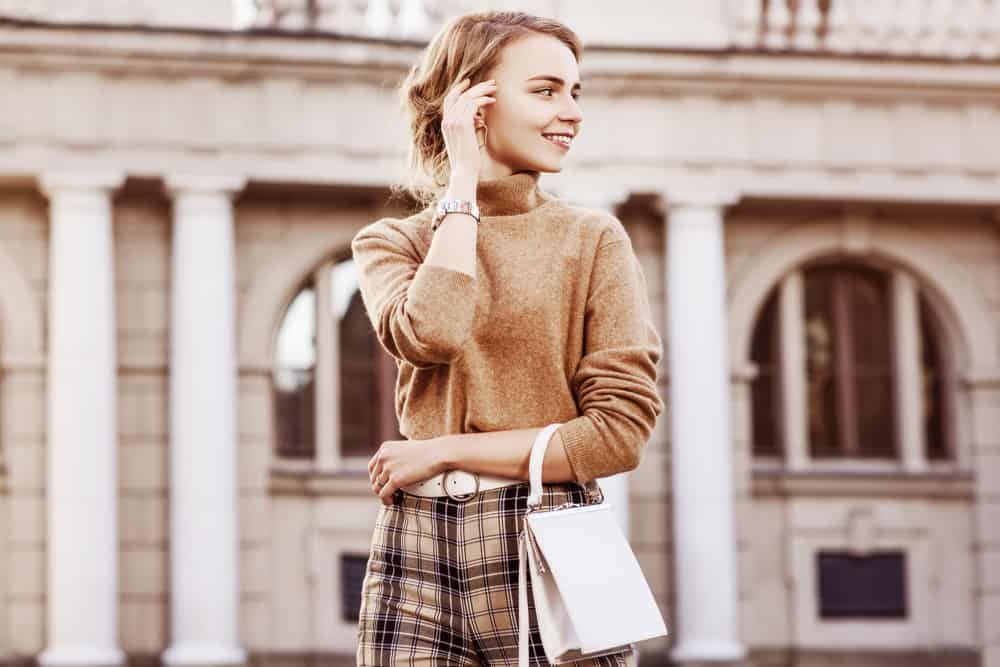 This is a close look at a woman wearing a brown cashmere sweater outside.