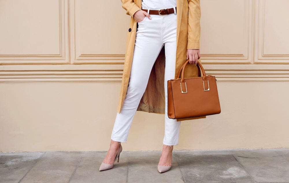 A close look at a woman wearing a pair of white jeans with long brown coat.