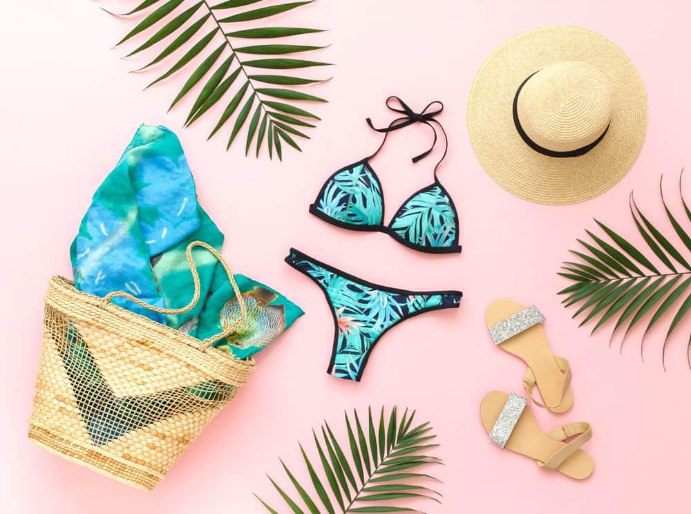 A tropical print bikini surrounded by beach accessories.