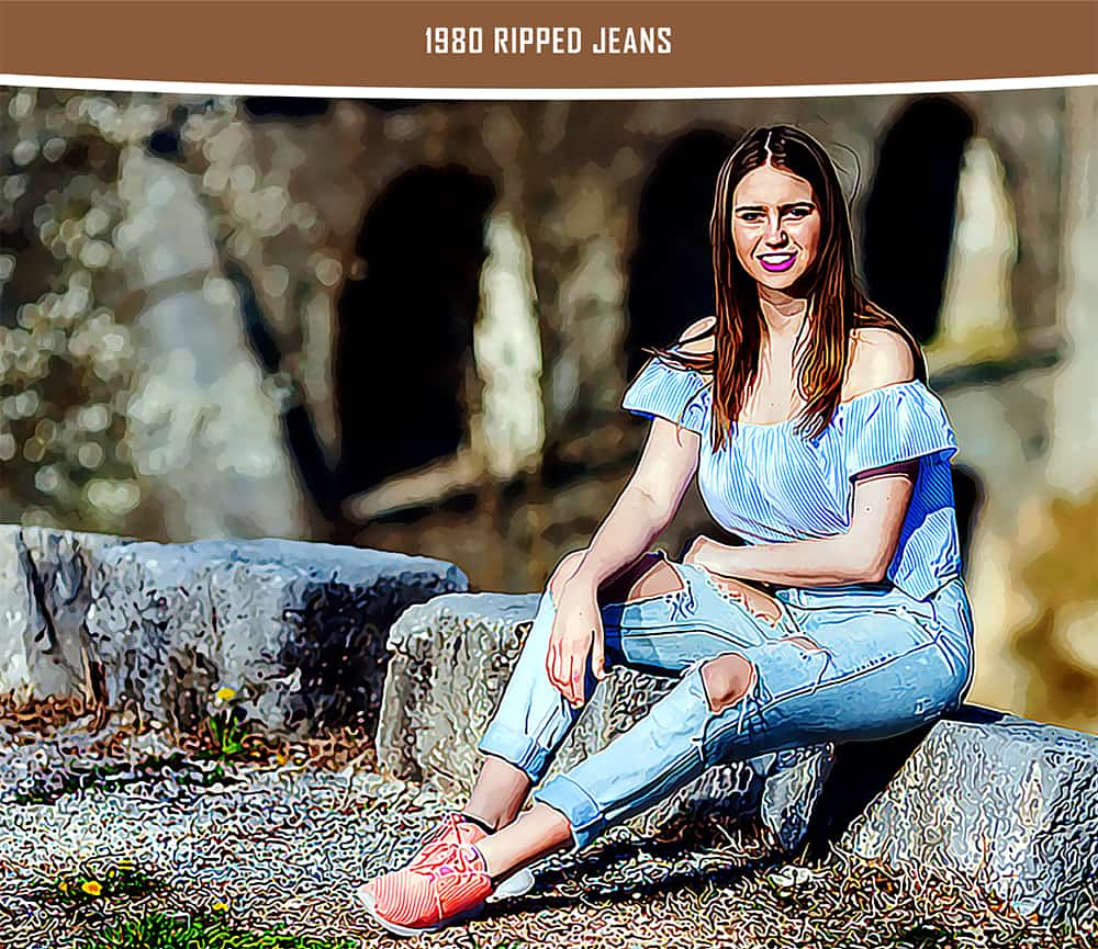 A woman wearing off-shoulders blouse and ripped jeans sits on a stone block.