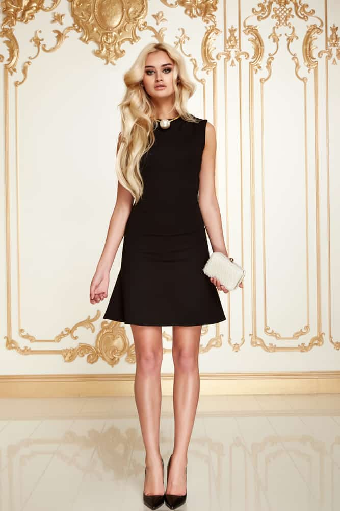 A woman wearing a little black dress and black shoes.