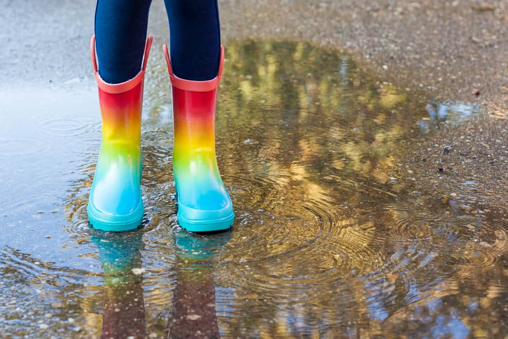 This is a close look at a child wearing a pair of rainbow rubber boots.