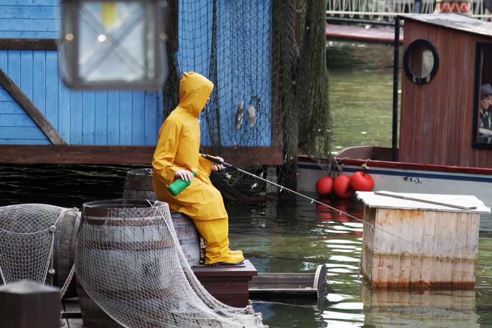 A man fishing at the docks wearing yellow rain gear.