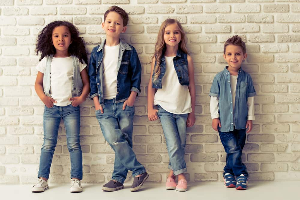 A row of kids wearing jeans.