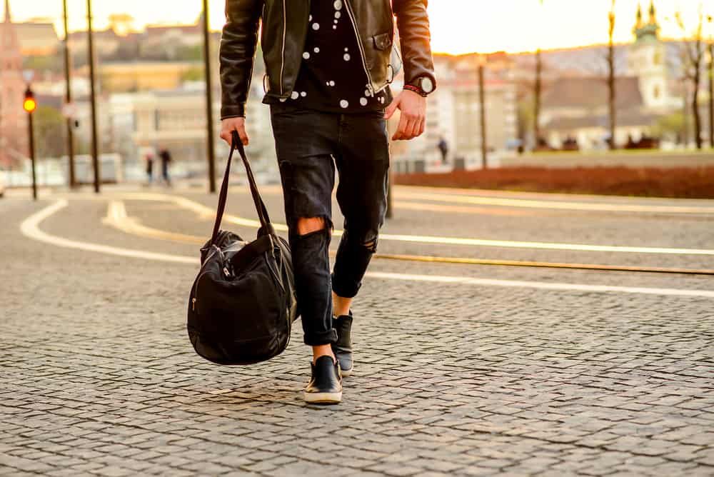 This is a man wearing a pair of ripped black jeans, black shirt and a brown leather jacket.