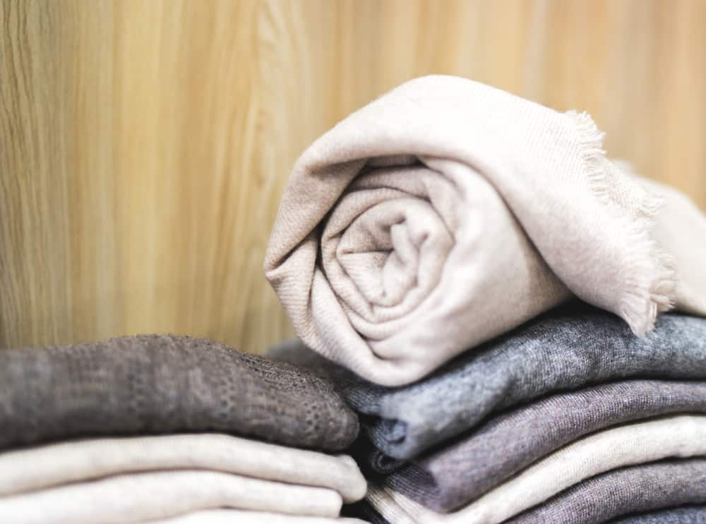 This is a close look at a stack of cashmere clothes with one rolled up on top.