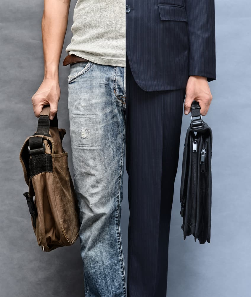 This is a close look at a man wearing half casual and half formal clothes.