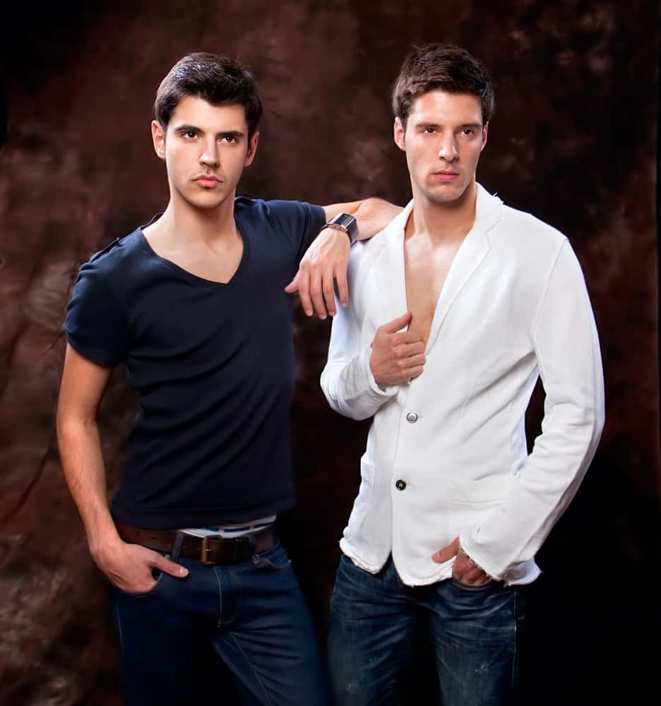 A couple of men wearing shirts and denim pants.