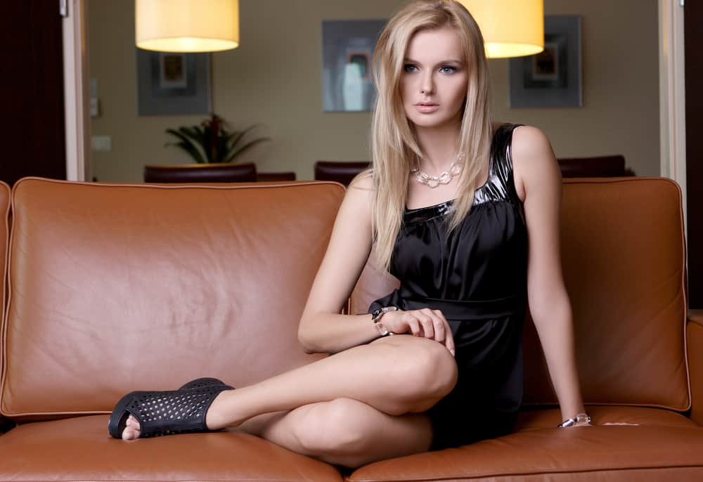 A woman wearing a little black dress sitting on the couch.