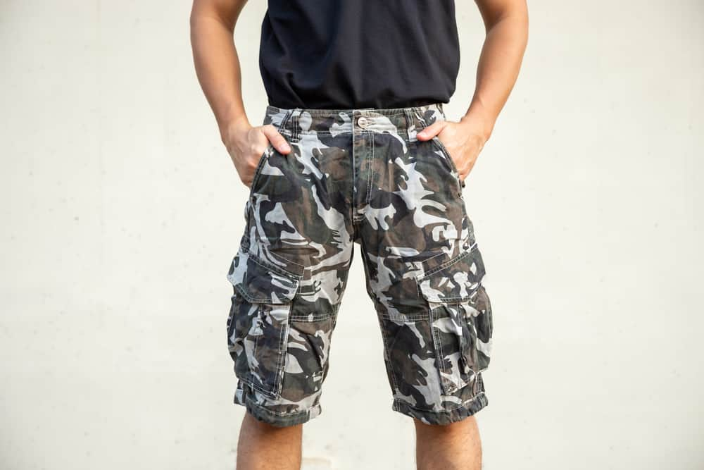 A man wearing a pair of camouflage print tactical shorts.