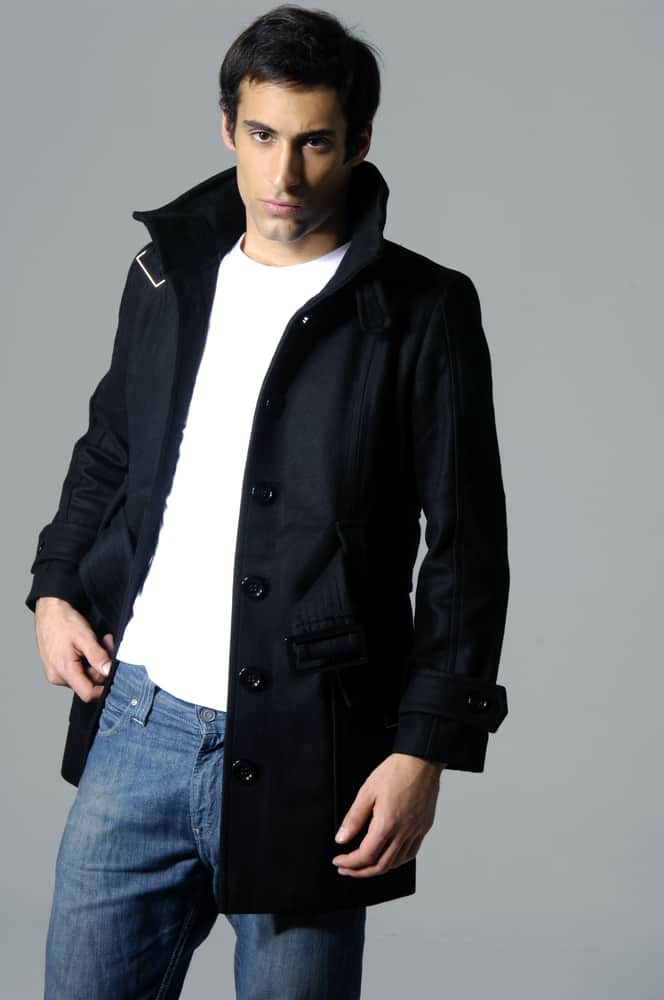 A man wearing a black jacket over his white shirt and denim jeans.