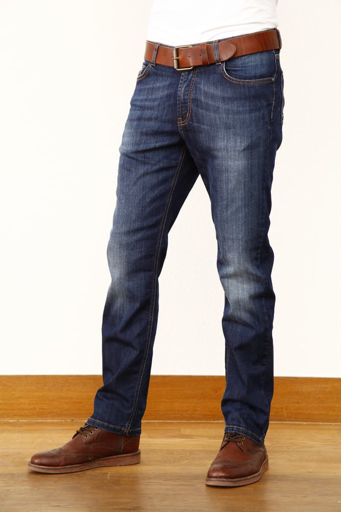 This is a close look at a man wearing jeans and brown leather shoes.