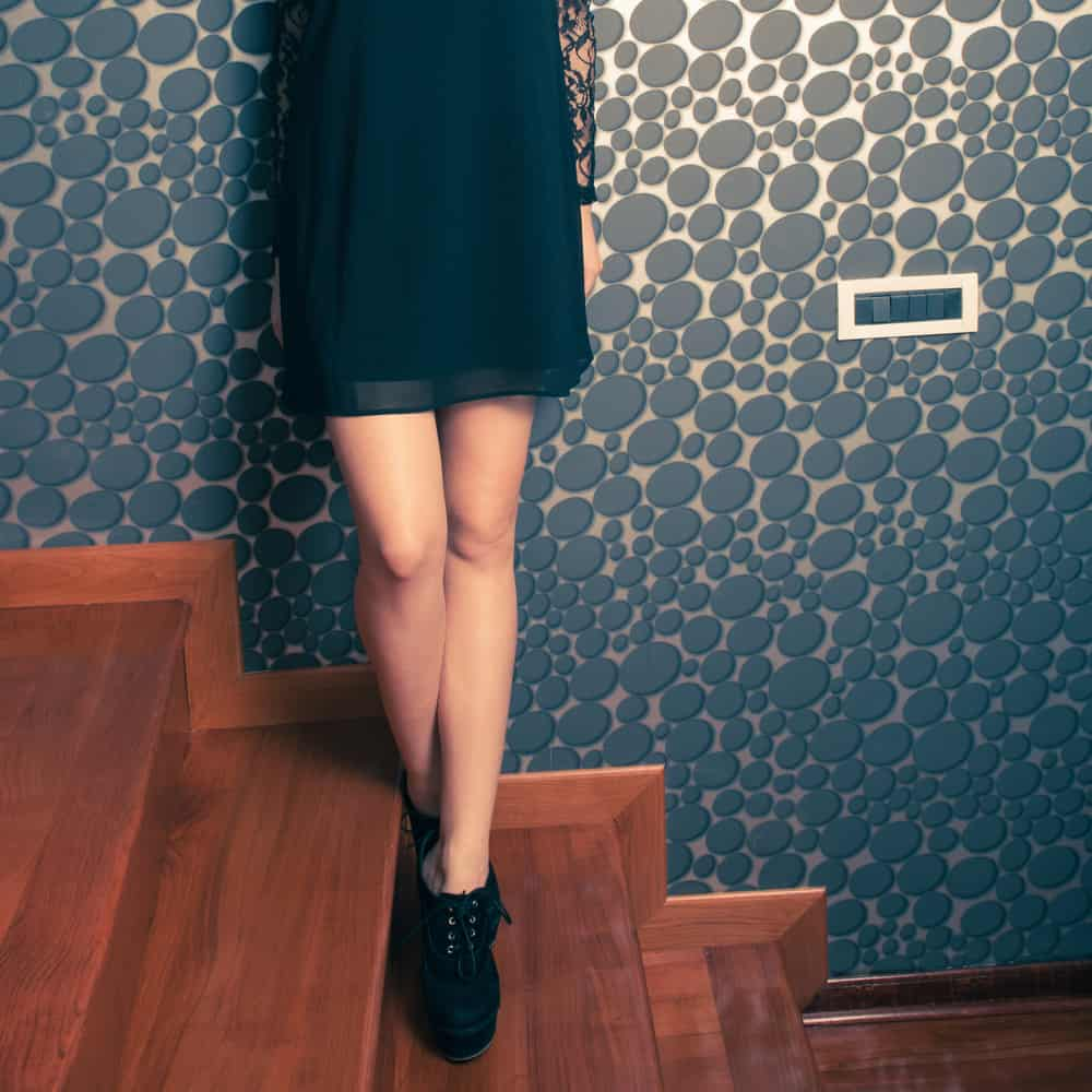This is a close look at a woman wearing a little black dress standing on the staircase.