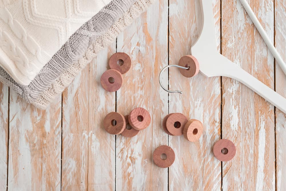 This is a close look at a wooden clothes hanger with cedar rings.